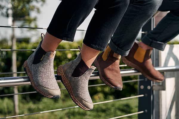 zwei personen sitzen auf einer stange mit sneakern