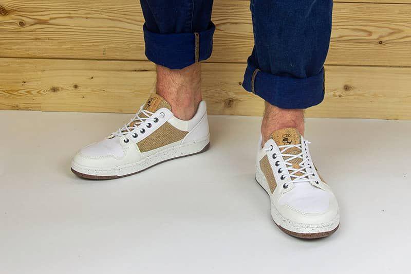 weisser sneaker vor holzwand
