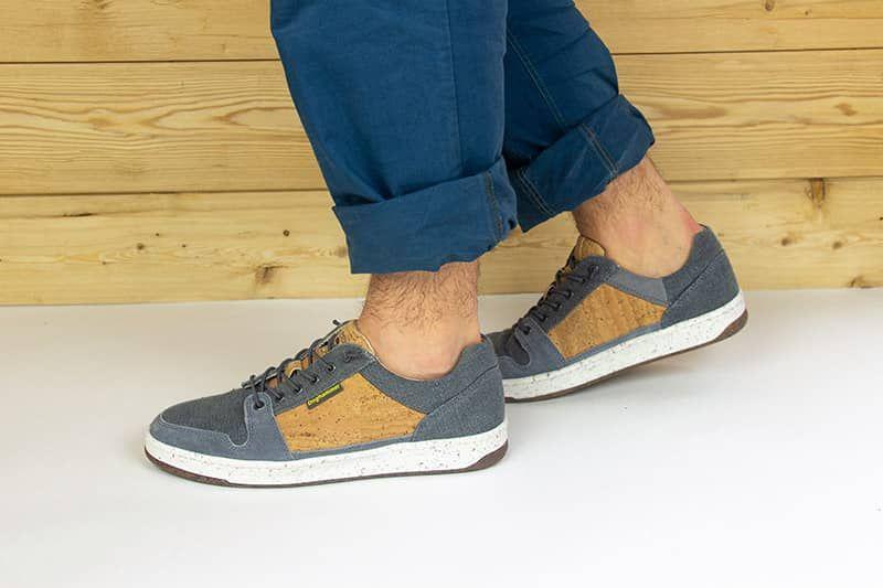 grauner sneaker vor holzwand